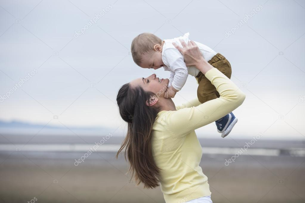 Mother and baby boy walking at beach