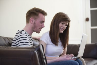 Couple relaxing in sofa with laptop