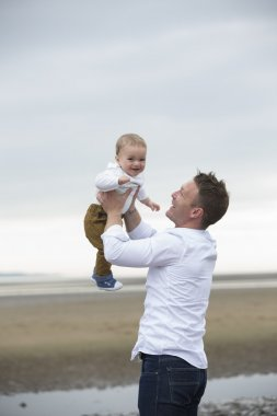 Dad and baby son playing at beach