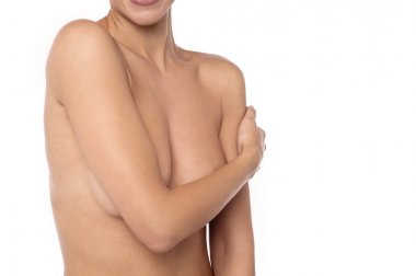 woman covers her bare breasts