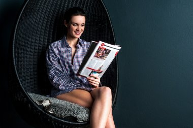 Woman on chair reading magazine