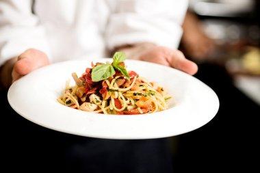 Chef hand holding pasta dish