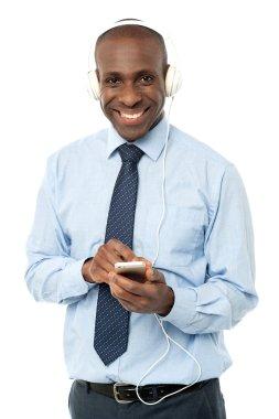 male executive enjoying music on mobile phone