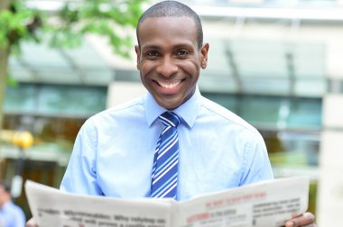 businessman smiling with newspaper