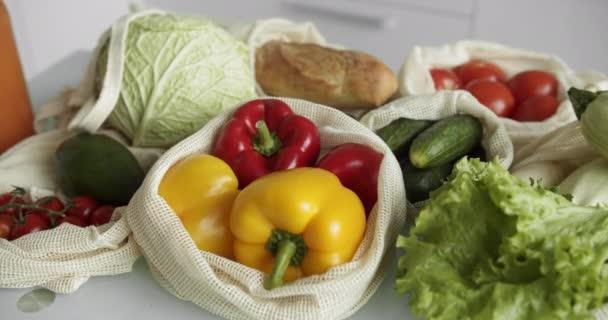 Zöldségek, gyümölcsök újrahasznosítható vattacsomagban az asztalon. Zéró hulladék vásárlási koncepció. Műanyag szabad tárgyak. Többcélú felhasználás, újrafelhasználás, újrahasznosítás. Környezetbarát vászonzsák paradicsommal, borssal, kenyérrel.