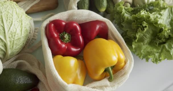 Zelenina, ovoce v opakovaně použitelných ekologických bavlněných sáčcích na stole. Nulový koncept nakupování. Bezplastové předměty. Multifunkční, opětovné použití, recyklace. Ekologická plátěná taška s rajčaty, pepřem, chlebem.
