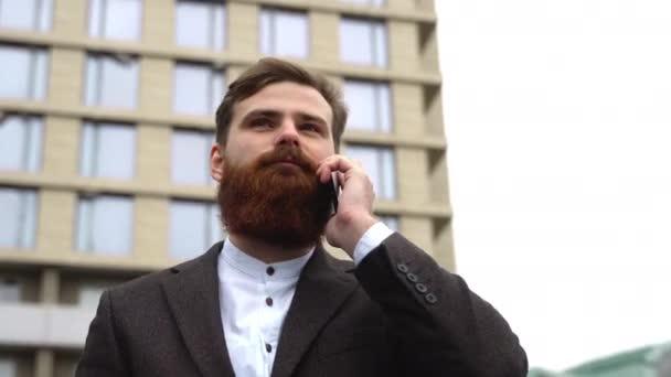 Obchodník telefonuje do finančního okrsku. Portrét mladého městského profesionála, který používá chytrý telefon nad kancelářskou budovou. Obchodník si venku povídá s chytrým telefonem. Technologie.