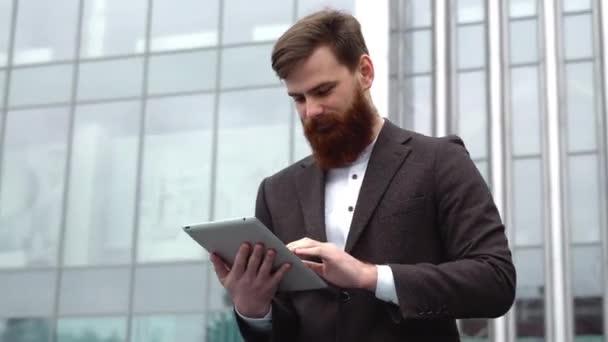 Moderní mladý vousatý obchodník pracující s digitálním tabletem. Mladý hipster obchodník drží tablet v ruce venku. Práce online s tabletem, zatímco stojíte venku na kancelářské budově.