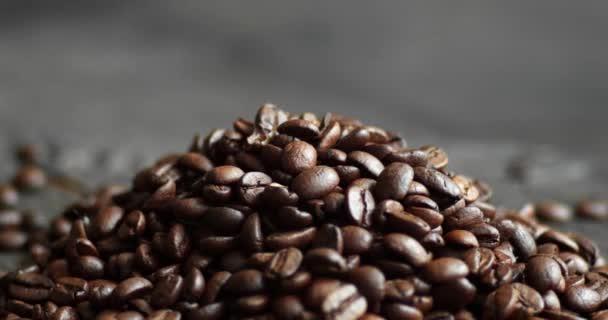 Pražená arabská kávová zrna roztroušená na dřevěném stole. Čerstvá kávová zrna. Espresso, americano, doppio, cappuccino, latte. Robusto. Selektivní zaměření.