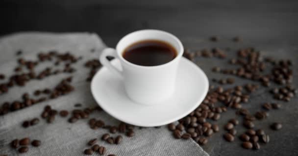 Bílý šálek kávy s praženými kávovými zrny roztroušenými na dřevěném stole. Hrnek čerstvé černé kávy. Čerstvé arabické pražené kávové zrno. Skvělý začátek dokonalého rána. Espresso, americano, doppio.