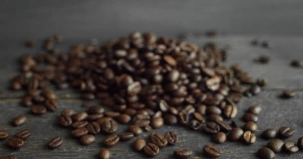 Roasted arabica coffee beans scattered on a wooden table. Fresh coffee beans. Espresso, americano, doppio, cappuccino, latte. Robusta. Selective focus.