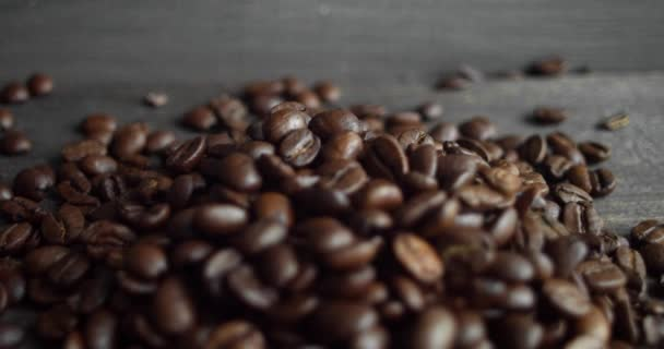 Pörkölt arabica kávébab szétszórva egy fa asztalon. Friss kávébab. Espresso, americano, doppio, cappuccino, latte. Robuszta. Szelektív fókusz.