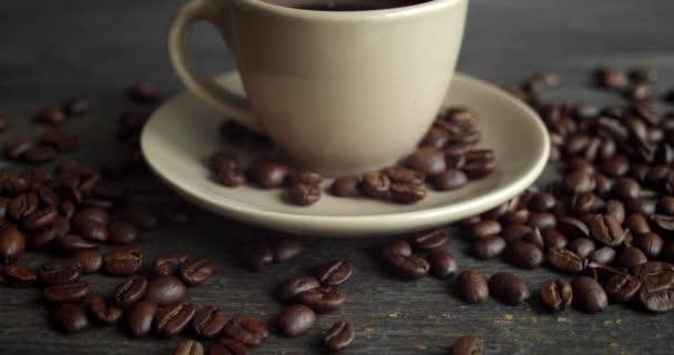 Šálek kávy s praženými kávovými zrny roztroušený na dřevěném stole. Hrnek čerstvé černé kávy. Čerstvé arabické pražené kávové zrno. Skvělý začátek dokonalého rána. Espresso, americano, doppio.