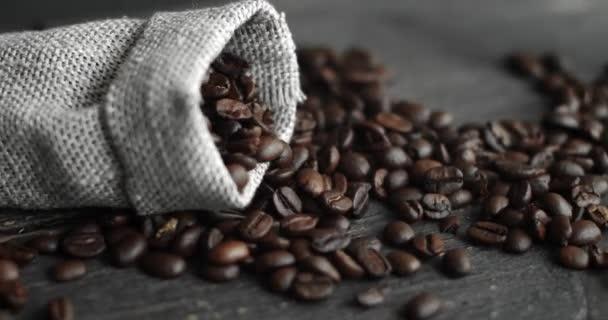 Kávová zrna roztroušená z plátěného pytle na dřevěném stole. Čerstvé pražené arabské kávové zrno. Espresso, americano, doppio, cappuccino, latte. Robusto. Selektivní zaměření.