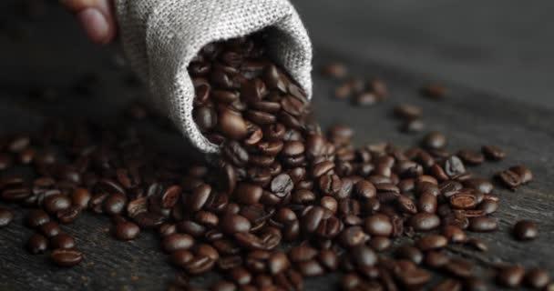 Mansova ruka rozptyluje pražená kávová zrnka z plátěného sáčku na dřevěném stole. Čerstvé pražené arabské kávové zrno. Espresso, americano, doppio, cappuccino, latte. Robusto. Selektivní zaměření.