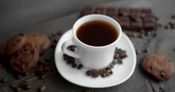 Šálek kávy se sušenkami, čokoládou a praženými kávovými zrny roztroušenými po dřevěném stole. Černý hrnek na kávu. Čerstvé arabické pražené kávové zrno. Skvělý začátek rána. Espresso, americano, doppio.