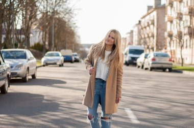 Amazing blonde girl walking alone on the road in old european city.