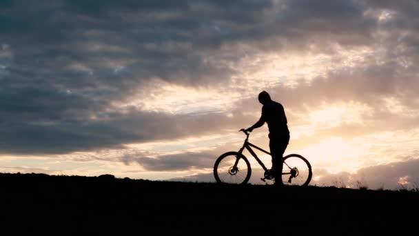 silueta profilu mladého muže, cyklistice cross kolo země na západ slunce
