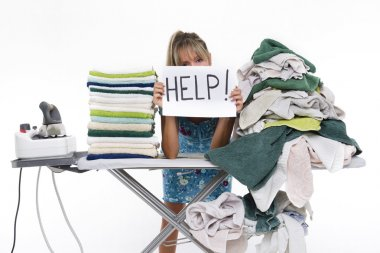 Woman behind an ironing board asks for help