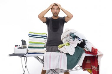 Desperate man with hands in his hair behind an ironing board