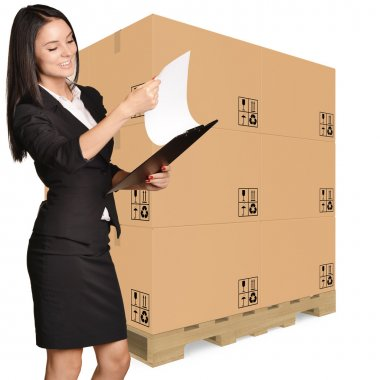 Office Girl standing with cardboard boxes on pallet and looking in clipboard
