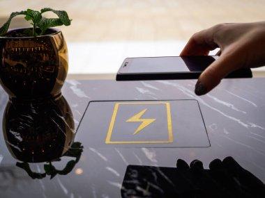 Bir kız akıllı telefonunu halka açık bir yerde kablosuz şarj istasyonu kullanarak şarj ediyor. Bir kadın telefonunu şarj ediyor ve modern teknolojileri kullanıyor. Kadınların elinde boşaltılmış akıllı telefon..