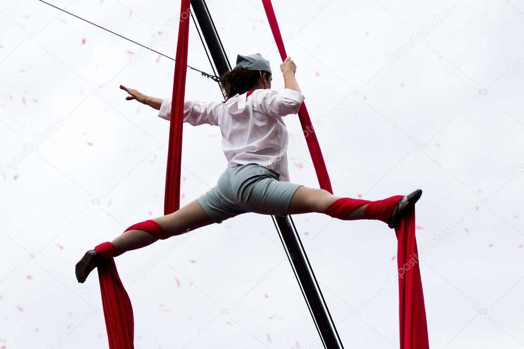 Young acrobat hung with her legs wide open.