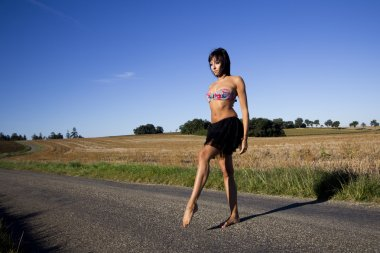 Barefoot woman crossing a road.