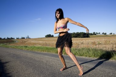 Dancer wearing a colored swimsuit top on a country road.