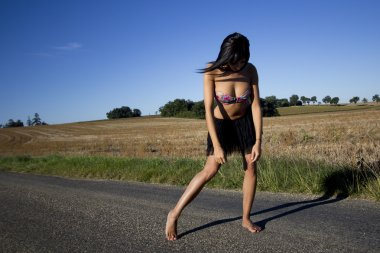 Defeated attitude of a barefoot woman on a country road.
