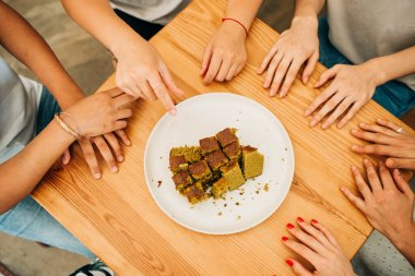 """Картина, постер, плакат, фотообои """"руки группы людей на деревянном столе и тарелке с кусочками торта"""", артикул 438920928"""