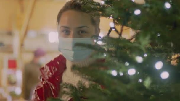 Fiatal barna, orvosi maszkban és vörös bundában a karácsonyfa mögött nézi. Ünnepi homályos fény a háttérben. Panned 4k videó kiváló minőségű felvételek.