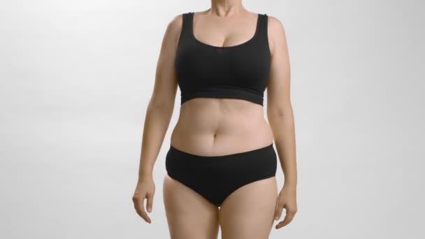 Bělošská nadváha samice ve spodním prádle ukazuje, jak pózovat pro kameru. Předtím a potom. Snímek statického videa.