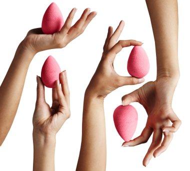 Hands holding makeup sponges