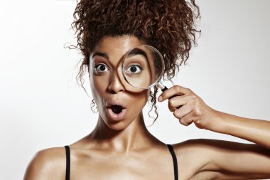 Woman with eye wathing in magnifying glass