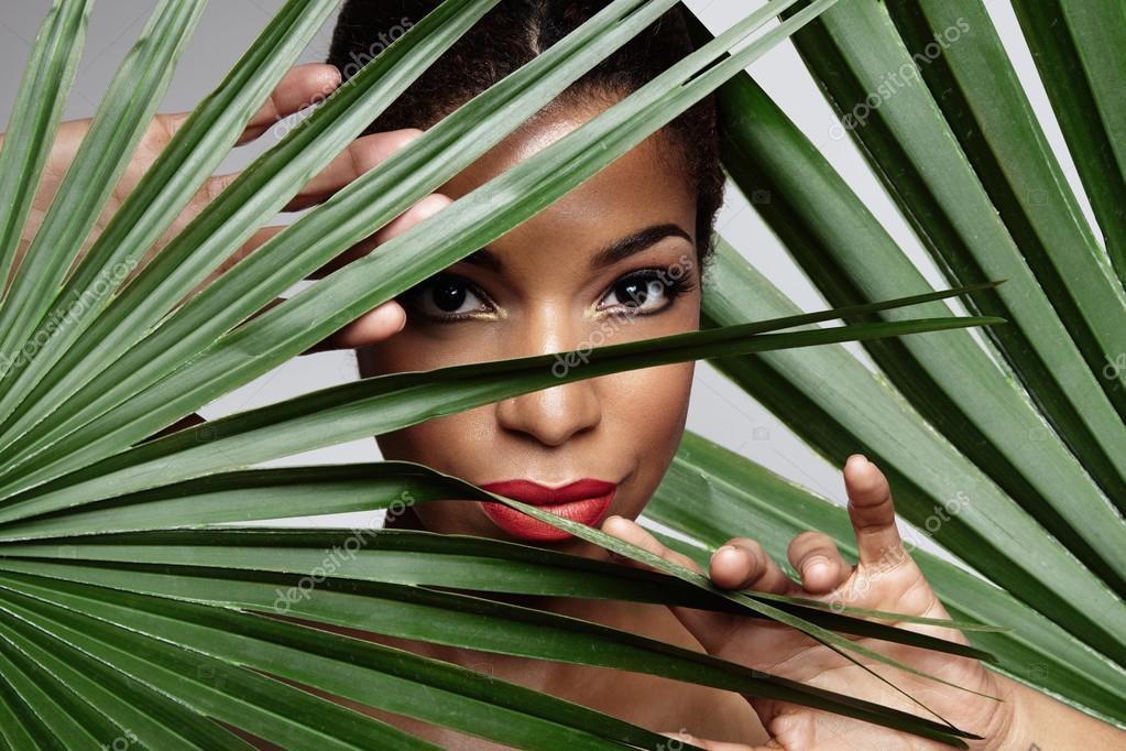 Woman between posing palm leaves