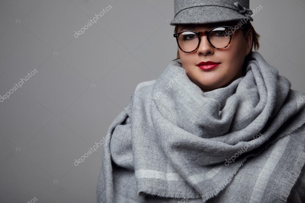 7a91db72a4e83 Bastante más mujer de tamaño con sombrero gris y bufanda posando en el  estudio