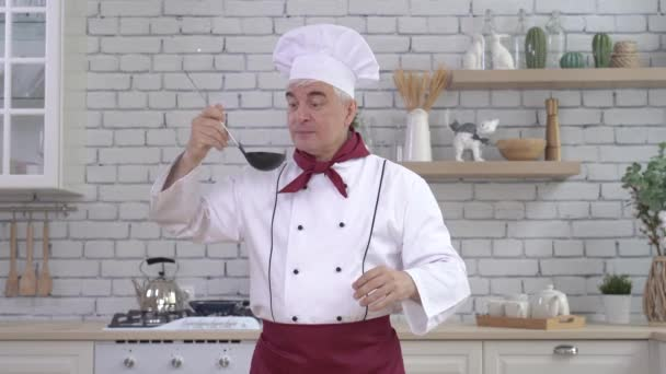 A férfi séf élvezi a leves illatát, és megkóstolja a konyhában lévő merőkanalból.