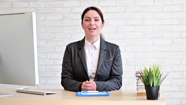 The female teacher sits at her desk and speaks to the camera. Online lesson