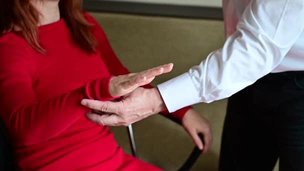 Eine rothaarige Frau sitzt mit geschlossenen Händen und erhobenen Händen in einem Stuhl. Reifer männlicher Hypnotherapeut in der Sitzung mit einer Patientin. Alternative Medizin für psychische Gesundheit. Beschnitten.