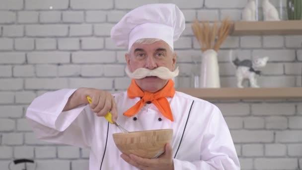 Egy idős férfi séf tojást korbácsolt egy fából készült tálba. Az öregember a konyhában dolgozik..