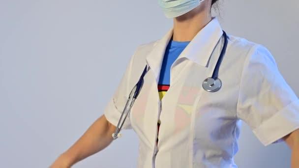 12.07.2020 Oroszország, Novoszibirszk: Orvosi maszkot viselő női orvos gombolja ki a kabátját és fedje fel a Superman öltönyt.