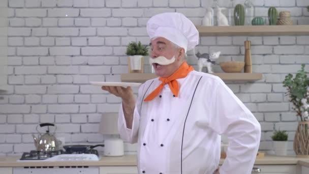 Egy barátságos, idős séf tányért tart a konyhában. Egy ősz hajú férfi vastag, ősz bajusszal dolgozik a konyhában.