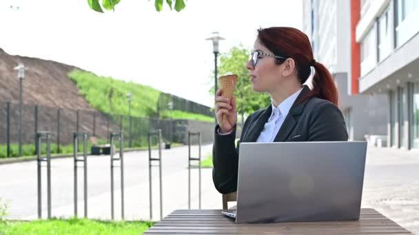Obchod sedí na letní terase s laptopem a šťastně jí zmrzlinu.
