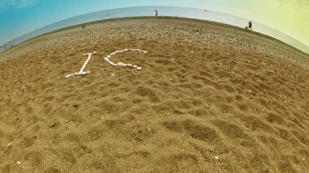 Phrase I LOVE SUN made from white stones appears on the beach sand