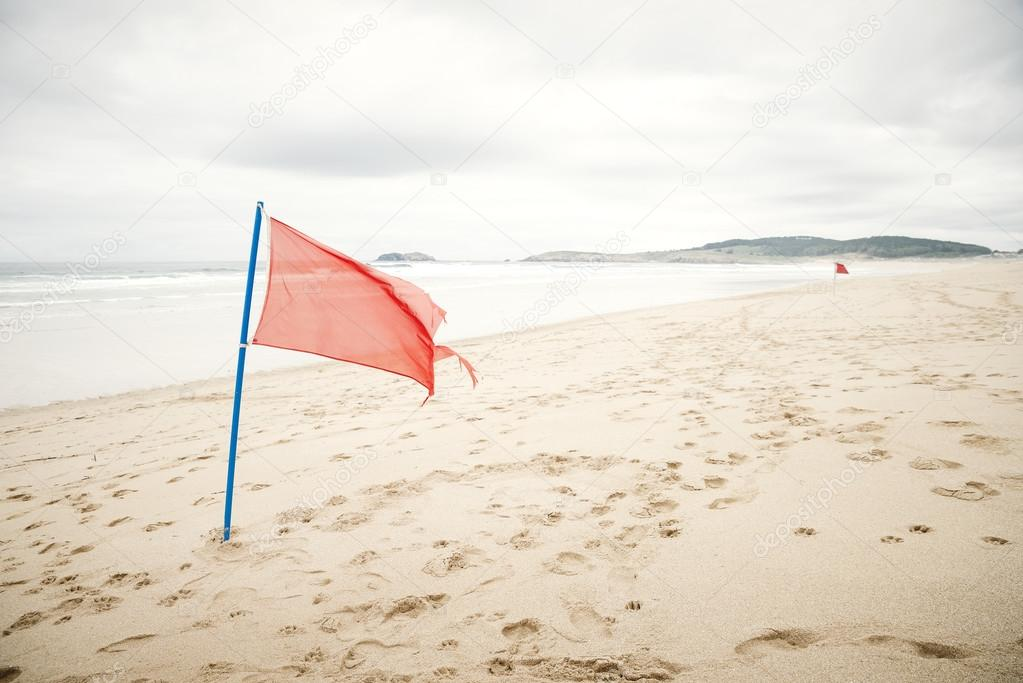 Warning sign of a red flag at a beautiful beach with a cloudy sk