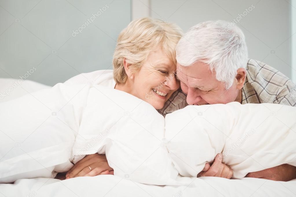 couple de personnes g es ludique au repos au lit photographie wavebreakmedia 102588034. Black Bedroom Furniture Sets. Home Design Ideas