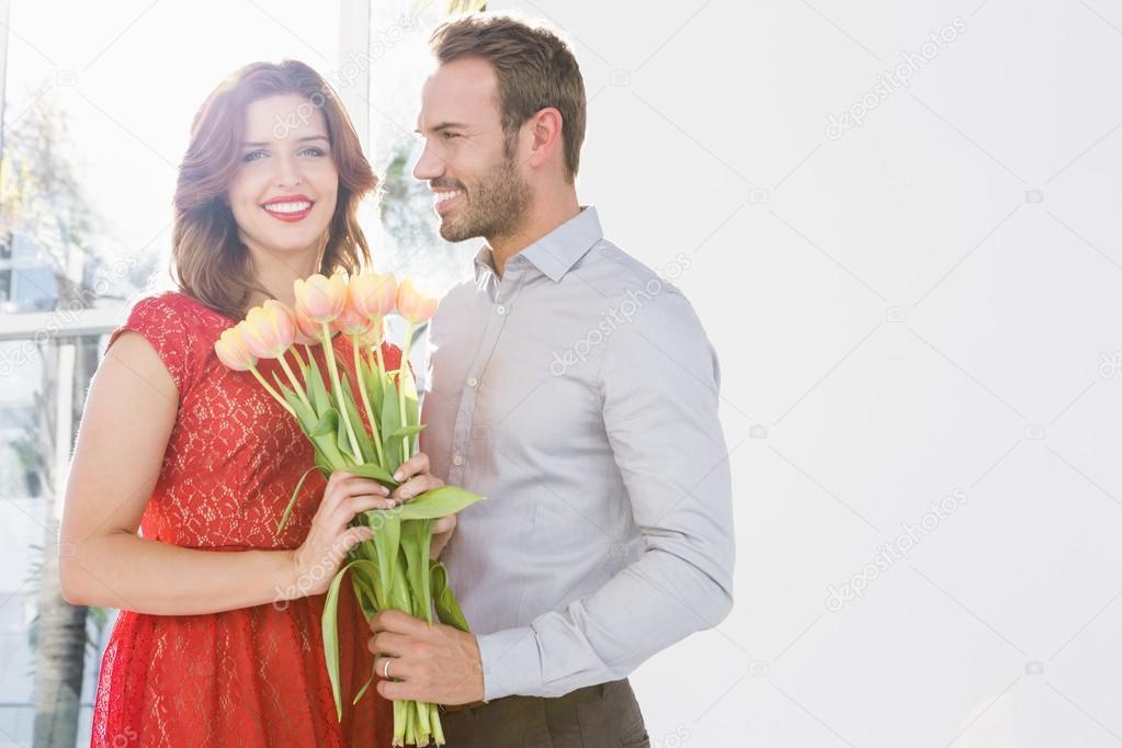 homme offre le bouquet de fleurs pour femme photographie wavebreakmedia 102609196. Black Bedroom Furniture Sets. Home Design Ideas