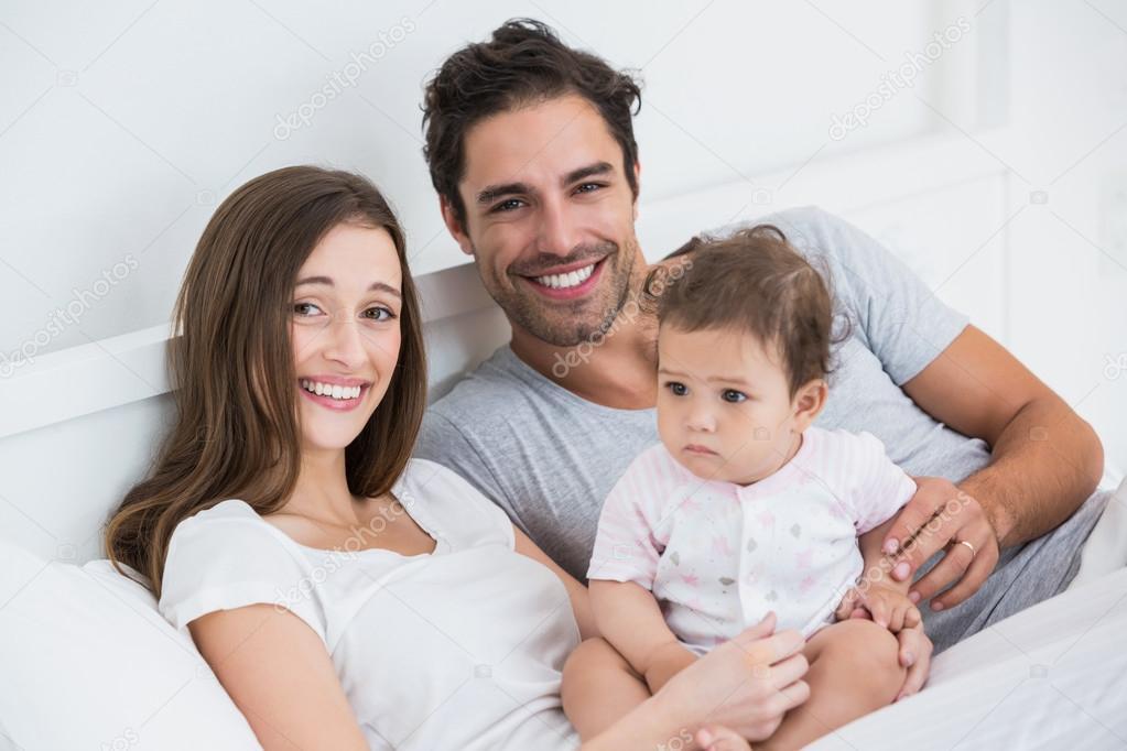 couple avec b b fille sur lit de repos photographie wavebreakmedia 102617152. Black Bedroom Furniture Sets. Home Design Ideas