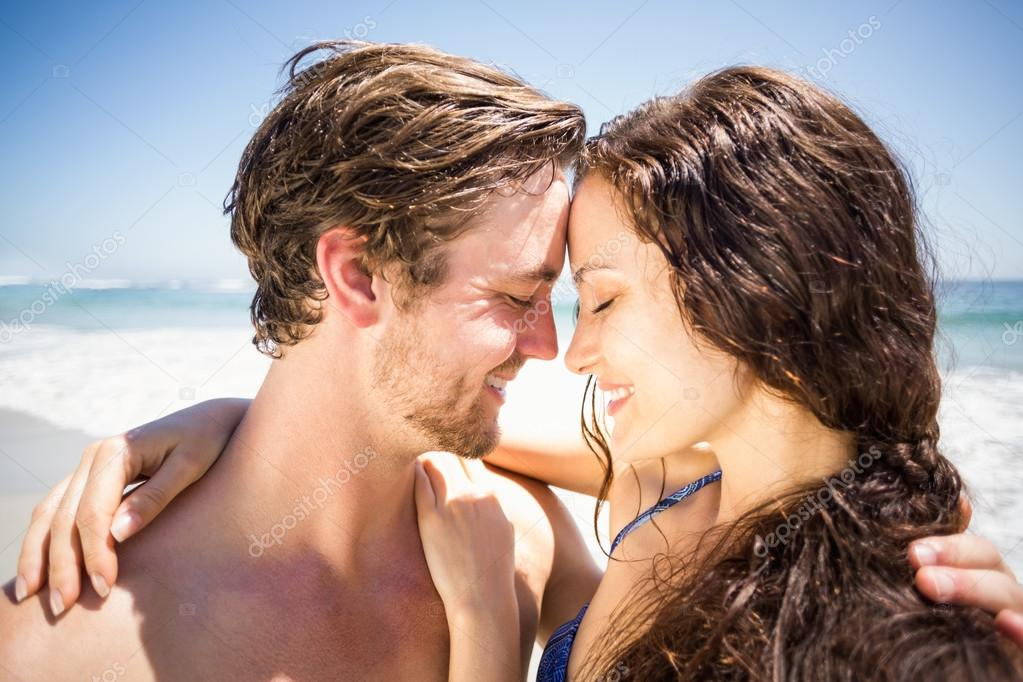 young couple romancing on the beach stock photo wavebreakmedia